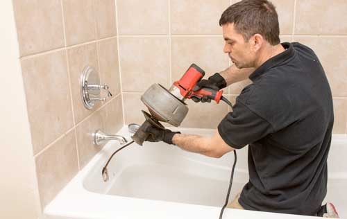 Plumber snaking a bathtub drain